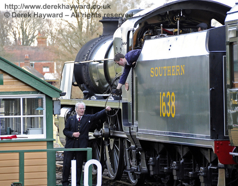 The crew of 1638 surrender the single line token as they pass Kingscote signal box.  19.02.2012  3588