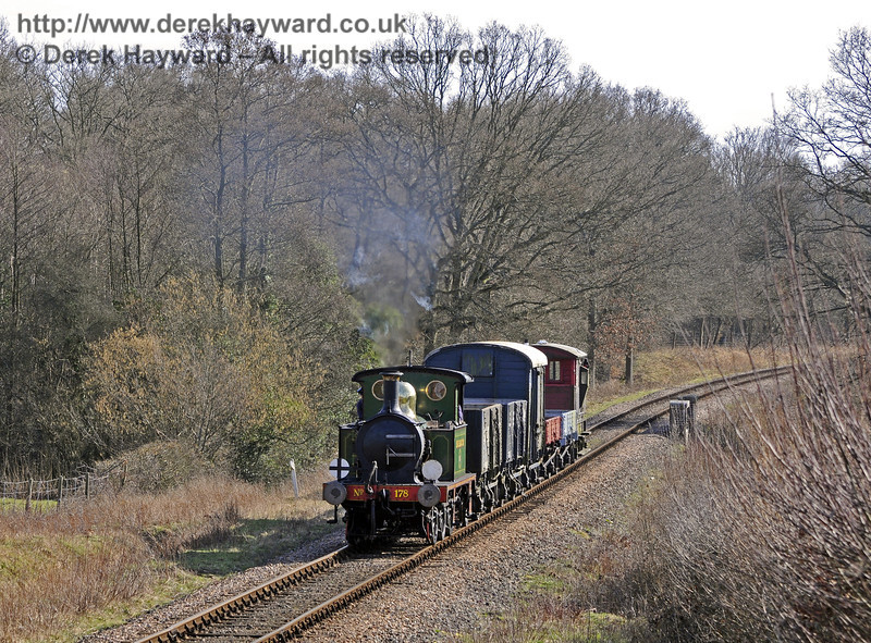 178 drifts north past Medhurst Farm with a goods train.  10.03.2012  7686