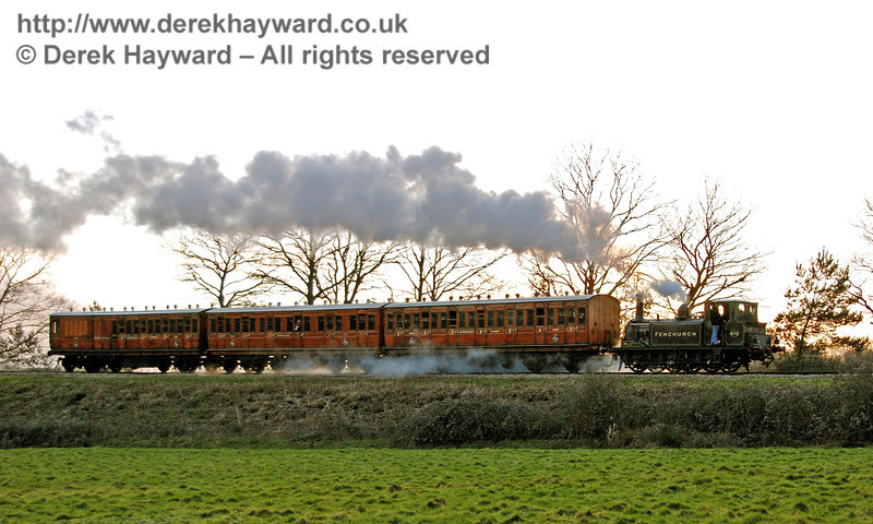 The sun is setting behind the train as 672 Fenchurch rounds the bend towards Horsted House Farm.  21.01.2007
