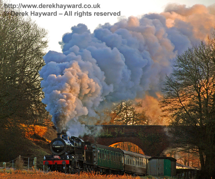Taken with a very long lens, the setting sun shines through Three Arch Bridge as 53809 climbs towards Horsted Keynes with a Santa Special. 07.12.2008