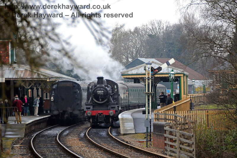 Seen from some distance away, passengers watch as 78019 runs round at Kingscote Station.  06.02.2010