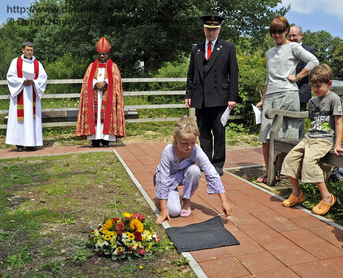 An engraved paving block is unveiled by Martin Eastland's granddaughter whilst Father John Twistleton (Rector of St. Giles' Church, Horsted Keynes, and the Railway's chaplain), The Right Revd Cornell Jerome Moss (Bishop of Guyana), BRPS chairman, Roy Watts, and other family members look on.  03.07.2011   2147
