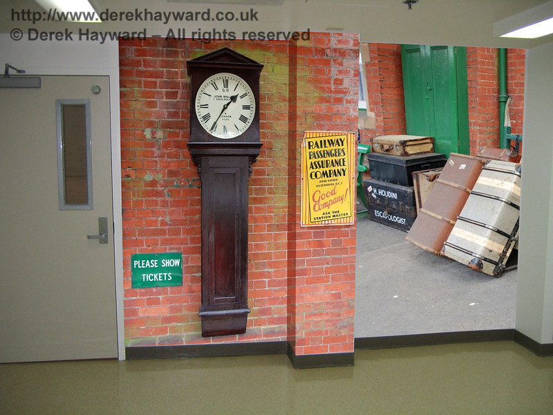 A mock up of one of the areas by a door including life size pictures of an actual clock, luggage and signs from Horsted Keynes Station on the Bluebell Railway.