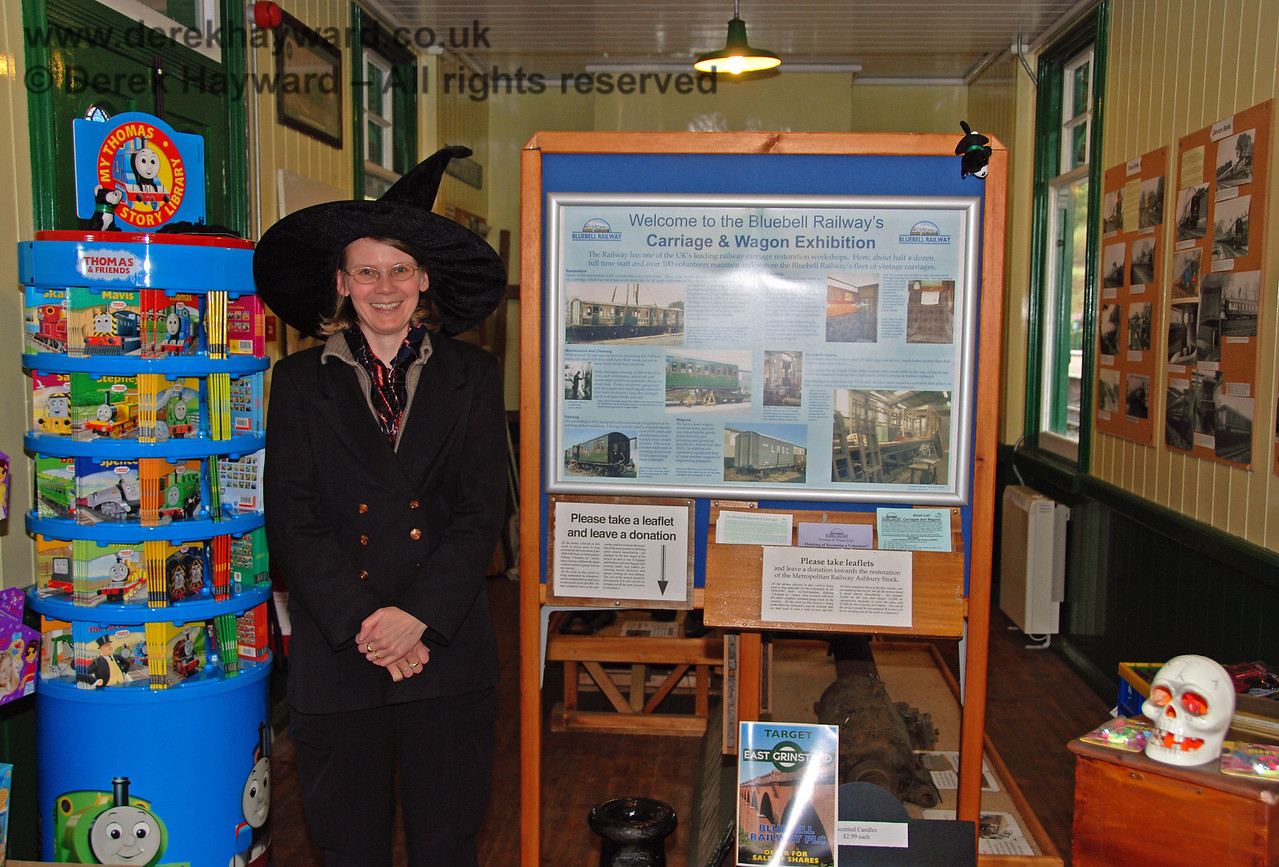 A smiling lady looks after the Carriage and Wagon exhibition and shop at Horsted Keynes.  That is not her normal headgear - it is the Wizard Weekend!  25.10.2008