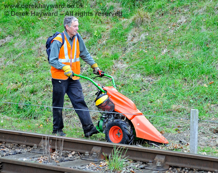 In 2015 the Friends of Kingscote acquired an unusual machine to help with cutting back lineside growth.  It is seen (not in use) en route back to Kingscote.  10.10.2015 12185