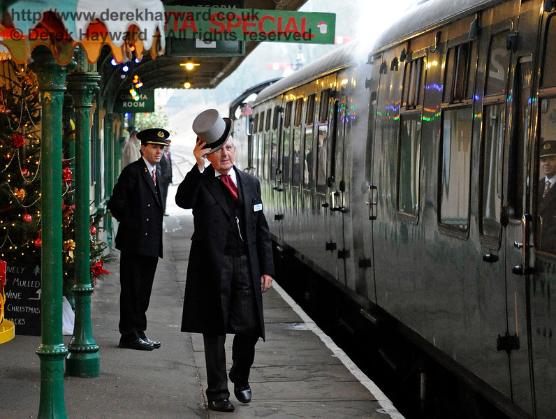 Roger Kelly doffing his hat, but undoubtedly not to me.  James Young watches and learns in the background (and also in the foreground as his reflection is caught in the coach).  Horsted Keynes 18.12.2016 14734