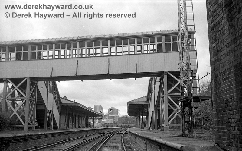 Ardingly Station captured on 12 April 1965 in some images taken by John Attfield.  John retains all rights to these images but has kindly allowed me to use them on my site.  The reverse of the previous photo, looking west along the platforms from the footbridge.  The signal box is in the distance and behind it are some of the industrial buildings in the stone plant.  On the right the very tall signal post originally carried two arms; one at high level and one very close to the platform for sighting purposes.