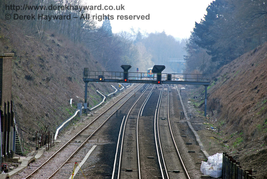 Copyhold Junction, looking south with a long lens.  The two main signals control the main line, with a permanent yellow colour light for the goods line.  The main signal for the goods line is beyond the gantry.