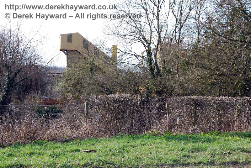 Some of the industrial buildings on the Hanson site can be glimpsed through the trees.
