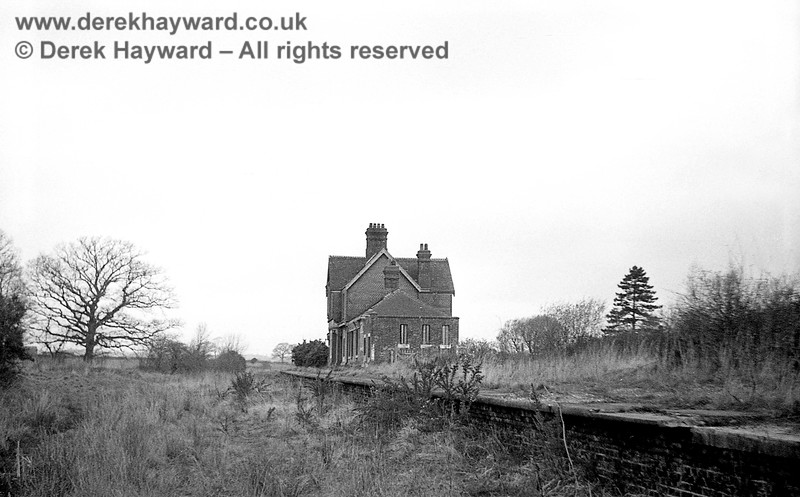 Barcombe Station pictured on 12 April 1965 looking north, with the remains of the station (then neglected) on the right.  Barcombe only ever had a single platform.  Contrast this image with later photos of the restored station.  John Attfield retains all rights to this image.