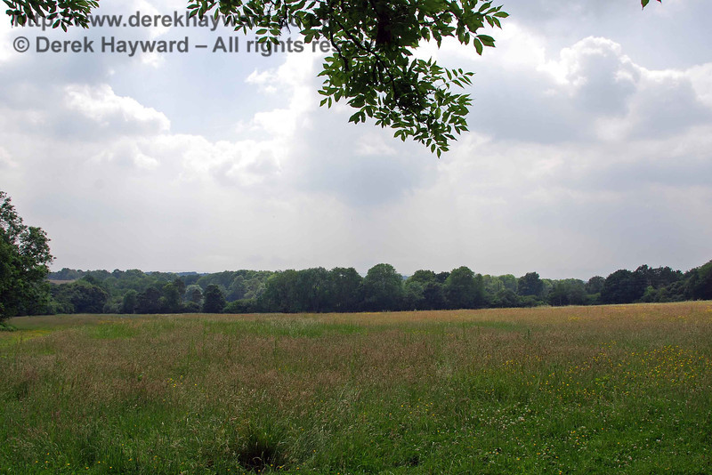 Despite the passage of over 50 years the embankment still makes its mark on the landscape, here running north as a line of trees to the south of Cinder Farm (viewed from the east).