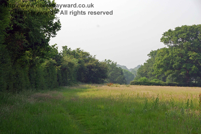 Looking north from the same position, the trackbed is within the trees to the left.  The V-shape in the distant tree line marks the path of the railway.