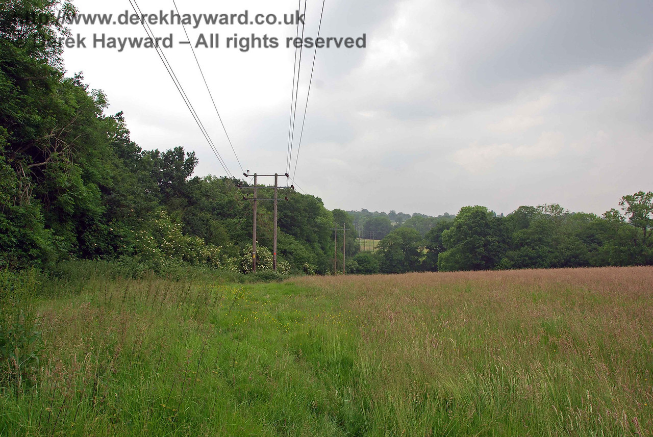 In this area the railway alternates between cuttings and embankments, with the power lines continuing their march along the eastern side of the line.  This view looks north from near Tutts Wood.