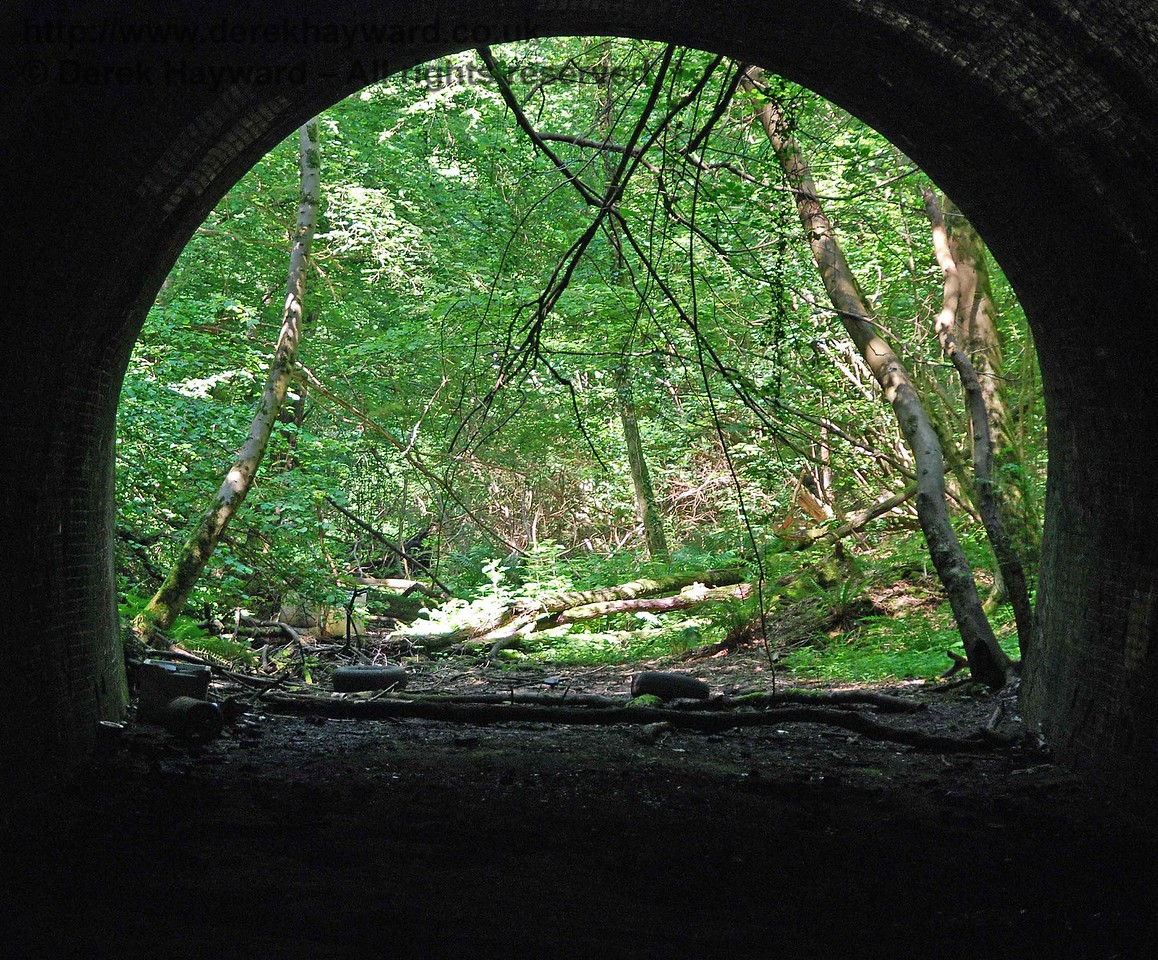 Within Cinder Hill Tunnel you can still see scrape marks on the floor where the demolition contractor extracted every last piece of ballast.  This view looks north through the tunnel with a long lens.