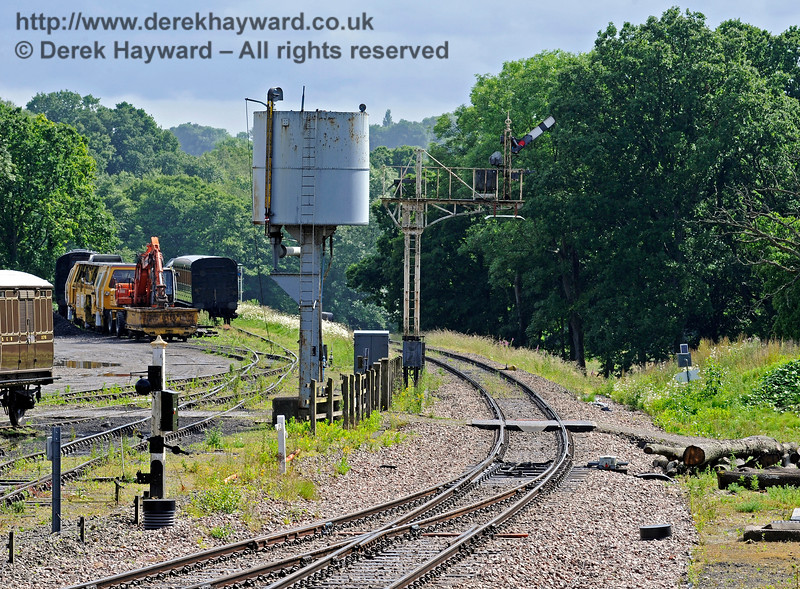 A similar picture of the Horsted Keynes Inner Home signal taken 10 years later and the scene is little changed.  The southbound advance starter has now been replaced, and the shortened post results in it being concealed by the coach in the Down yard.  The water tank has also acquired a little rust.  There is a brand new set of points.  25.06.2016 13444
