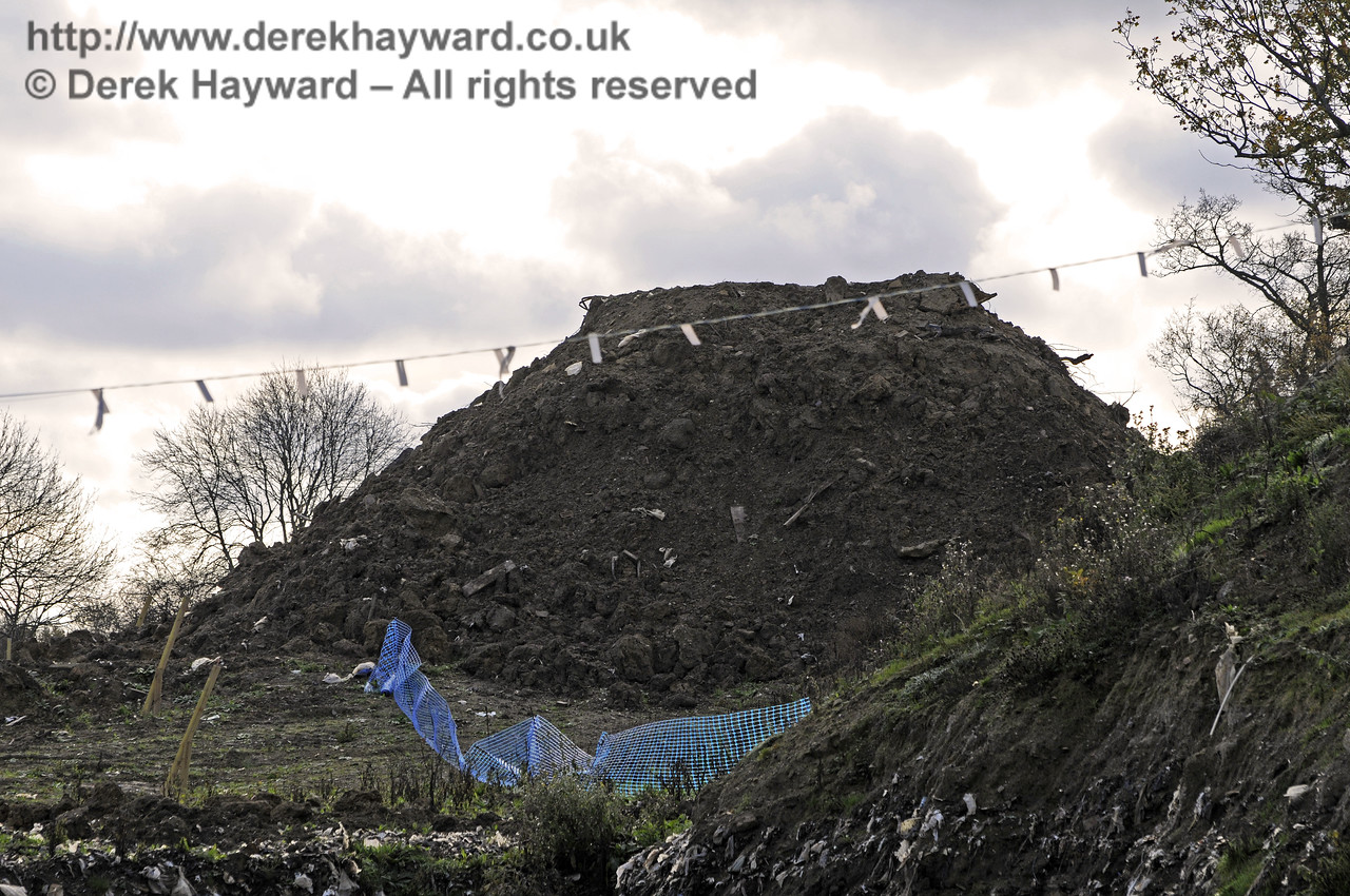 Looking south from Hill Place Farm Bridge at one of the piles of clay spoil removed to gain access to the rubbish..  24.11.2011  7597