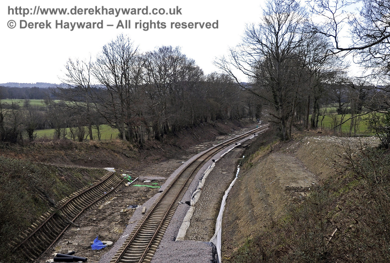By February 2013 the inert spoil had been used to raise the level of the track bed and the line had been relaid as far as Imberhorne Lane Bridge, following the installation of drains and services.  On the right an area of slipped embankment has been dug out and repaired, and on the left spare track panels are available to further extend the line under the bridge.  17.02.2013  6137