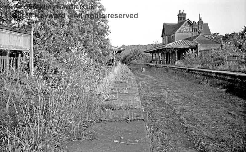 Kingscote station, looking south on 17 July 1966 after removal of the track.  Contrast the overgrown platforms with the immaculate station that the Bluebell Railway later created.   John Attfield retains all rights to this image.