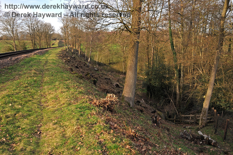Trains run on an embankment as they climb towards Three Arch Bridge, and a large culvert takes water under the railway here.  The eastern side of the embankment is seen after lineside clearance. 24.02.2011 6044