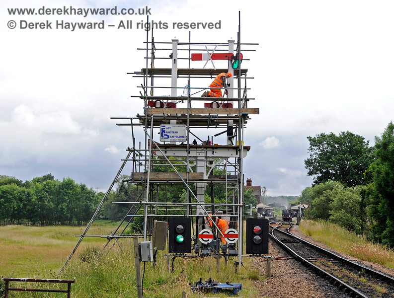 "The renewal of the Inner Home bracket signal in progress.  Whilst the signal was being reconstructed temporary colour light signals were installed to replace it.  An outgoing train is waiting in Platform 2, whilst the left hand signal shows a clear road into Platform 1 for an incoming southbound service.  Between the two colour light signals are ""Calling on"" ground signals, that permit entry into an occupied platform.  For example, these would be used when a locomotive was running round stock that had been left in the platform. 25.06.2017 17427"