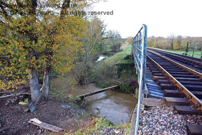 The western side of the River Ouse bridge, showing the river meandering alongside the track for a short distance. The flow is towards the camera.  15.11.2009 0105
