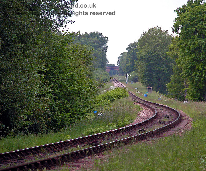 A view looking up Freshfield Bank from Ketches Halt towards the Distant signal.  The lens makes the distance appear shorter.  Just before the fogman's hut Palmer's Cattle Creep passes under the line.  The fogman's hut marks the original position of a signal. In the far distance is Town Place Bridge. 04.06.2006