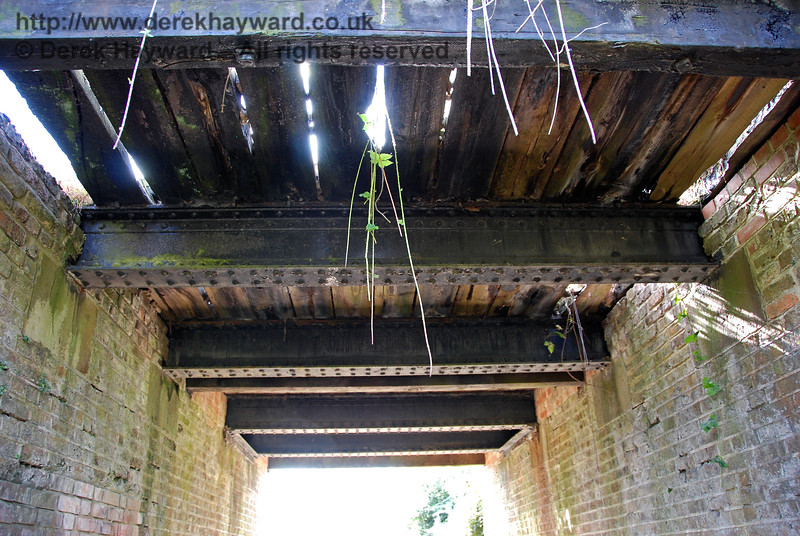 The underside of Palmers Cattle Creep pictured in 2007.  At first sight this looks a bit draughty, but the eastern end of the bridge has never carried any load, the track in this area being a single line since construction in 1882.  Careful viewing of the picture shows the iron girders supporting the track to be totally intact, with a solid base.  Nearest the camera, where there is no load, there is a wooden cross beam rather than iron, and the planking had seen better days. The rotten timbers were subsequently removed.  23.09.2007