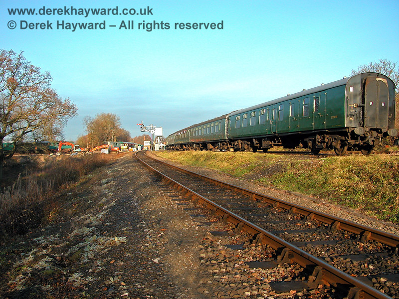 A view of the approach to Horsted Keynes in 2005.  On the right coaches stand in the Down Yard, and in the distance some work appears to be taking place adjacent to the Ardingly Spur.  However, at the time, the triangle appears to be empty of spoil. 11.12.2005