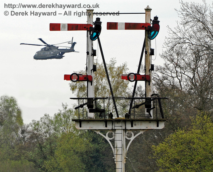 One of those shots where you are in the right place at the right time.  The Sheffield Park Inner Home bracket signal is pictured as a military helicopter passes by.  It is not that unusual to find helicopters overflying Sheffield Park. 14.04.2011 0727 (For those in doubt this is not photo editing trickery).