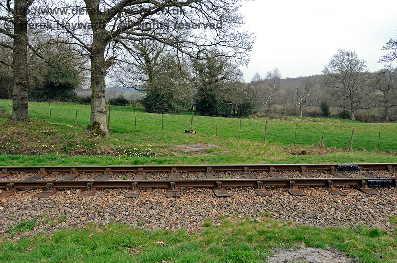 There is a short section of level ground between the embankment and the cutting, and this was the site of a long abandoned agricultural crossing. This view looks east across a section of flat ground which crosses a drainage ditch (which is in a pipe under what is effectively a bridge over the ditch). The lineside fences show no sign of the original gates but you can see the original route of the path in the shape of the adjacent land, particularly on the eastern side.  10.04.2015 12147