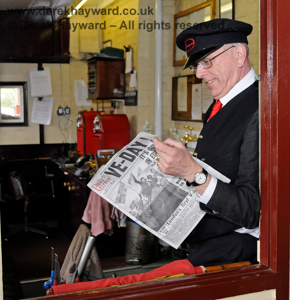 It is quite unusual to find a colour image from around VE Day, but the Signalman has aged well ever since.  The shot, actually from Southern at War on 10.05.2015, catches the red token machines and (above them) the signal telephone apparatus  in the background.  12502