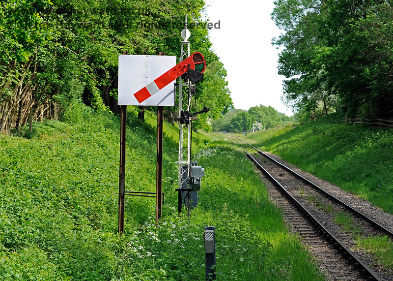 "The Sheffield Park Outer Home signal in the ""Off"" position. Approaching the signal on foot from the south the arm is now completely hidden and the signal therefore no longer serves as an early warning of the approach of southbound trains from around the bend.  On some other railways the sighting boards are positioned slightly lower, so the arm can be seen from the rear when the signal is ""On"". Drivers see a clear view of the arm with the white board below.  When the signal drops it is still highlighted to drivers, but northbound track walkers see it vanish behind the board, warning that the signal has changed to ""Off"". An example of this arrangement can be seen at Blue Anchor on the West Somerset Railway. 18.05.2018 16482"