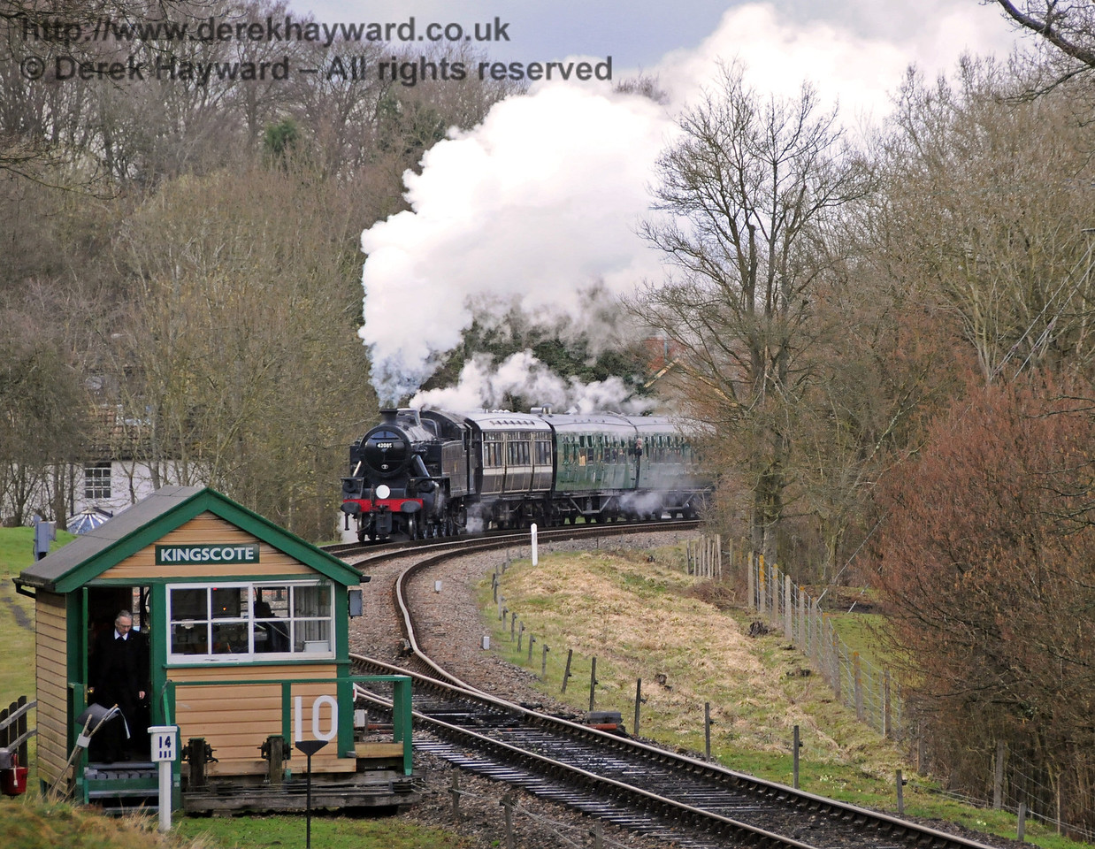 The signalman prepares to hand over the single line token, as, in the distance, 42085 leaves Kingscote.  27.03.2010  1715