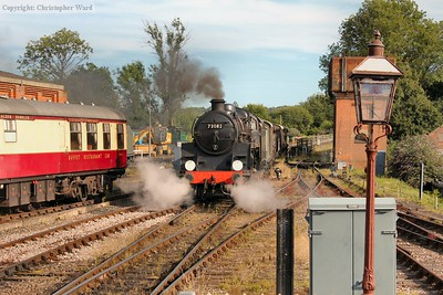 With much fuss, 73082 brings the freight out of the siding and into the station