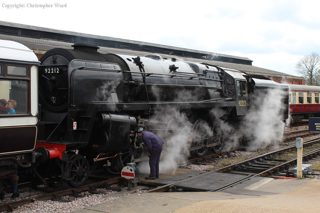 The driver checks the cylinders of the 9F as the engine is uncoupled