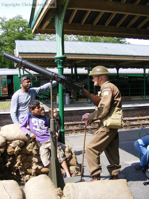 A Home Guard soldier tells the ensemble how the gun works