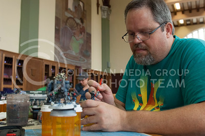 Stefan Yates, academic advisor for mechanical and nuclear engineering, paints miniatures for the game Warhammer 40,000 during board game day hosted by the Games CLUB in Hale Library in Mahattan, Kan. Nov. 4, 2017. (Justin Wright | Collegian Media Group)