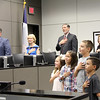 Students leading the pledge with board members participating in the background.