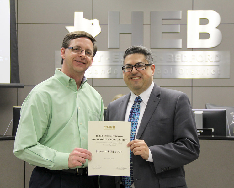 Board member Fred Campos and Trinity High School principal Mike Harris, in recognition of a donation from Brackett & Ellis, P.C.