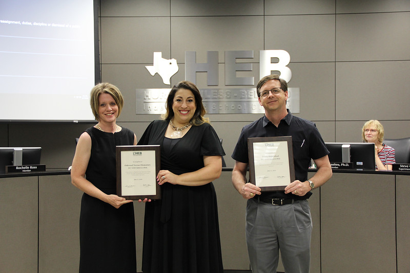 School administrators hold awards for the success of at-risk students.