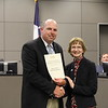 Central Jr. High principal Randy Belcher with Faye Beaulieu, holding a donation certificate recognizing Myles Turner/MTX Management