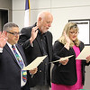 Fred Campos, Andy Cargile, and Julie Cole read their oath of office with right hands raised, signifying the beginning of their new terms as school board members.