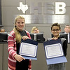Aftynne May and Tristan Collins holding certificates of recognition for leading the Pledge of Allegiance.