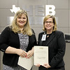 Board Member Julie Cole with the principal of Hurst Hills Elementary, recognizing a donation from Crimson Building Co, LLC.