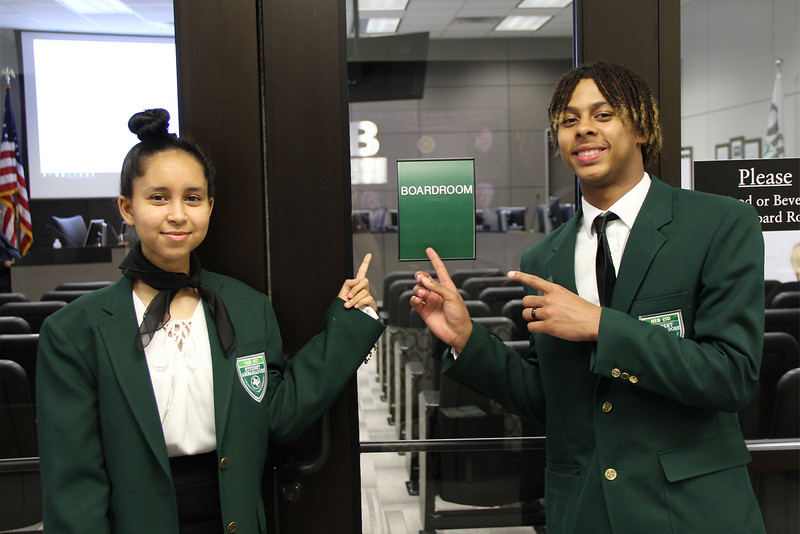 Two HEB ISD student ambassadors point to the sign outside the boardroom