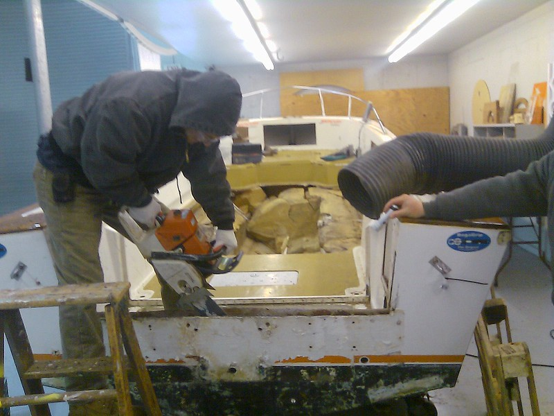 1/2/2010<br /> <br /> In order to finish the hogging out of the transom we needed a bigger chainsaw. Here is a new volunteer Joe with his 24 inch saw getting down to the bottom of the transom.