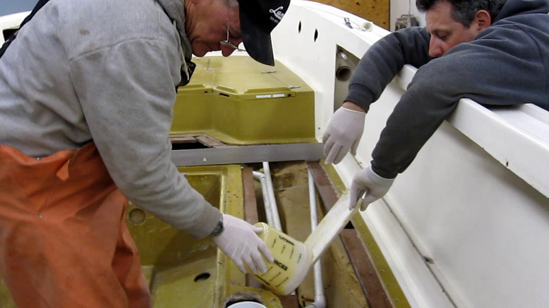 """2/11/2010<br /> <br /> Pouring foam to nest the gas tank coffin to the bottom of the boat. With all the weight of a full gas tank you have to support it with something really strong but flexible. We poured 4 pound foam under the coffin to take the load. It worked real will with a good bond and solid support.<br /> <br /> The foam is tough to work with. We had to heat it with a heat gun to get it warm for maximum expansion. We also had to use the """"Gazooba"""" tool to get it to flow into a small space.<br /> <br /> All worked well and it was a good day."""