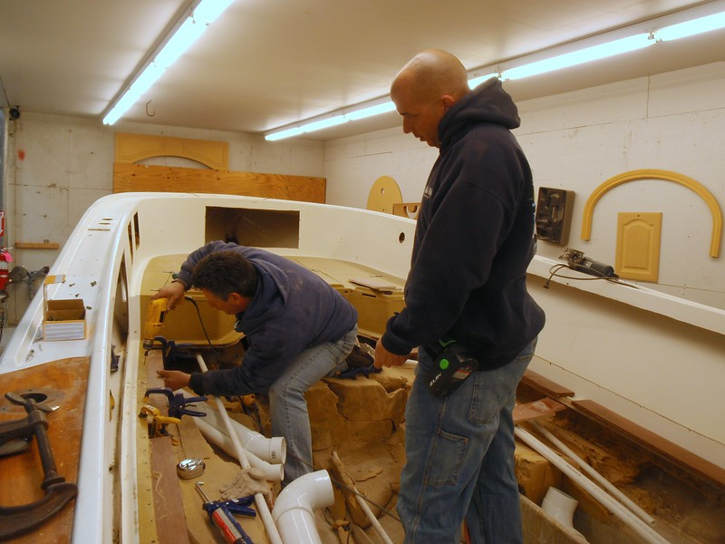 2/5/2010<br /> <br /> Captain Dave Zarrello stoped by today to lend a hand with the project. <br /> <br /> Cleating the edge of the deck and the coffin needed a lot of hands. Not hard work but tedious with lots of steps. Drill, countersink PL400 and screw. <br /> <br /> Things worked out well and we got most of it done. Here is George and Dave mounting the cleats to the outboard side of the deck.