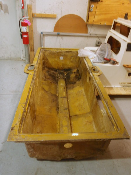 This is the tub that was nested between the inner stringers in which the two gas tanks were mounted in foam and screwed to the sides. This tub was part of the deck and inner lining. It is laid up glass and we will reuse it. Notice the dark patch at the back of the tub which was aft. It was holding water which was causing the pitting in the aft tank bottom.