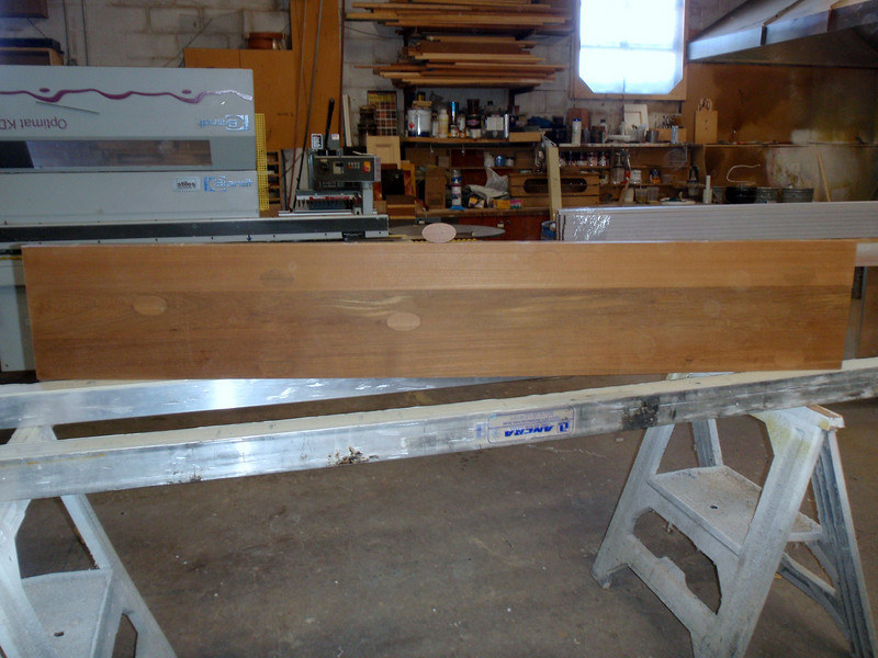 """2/11/2010<br /> <br /> Today I went to inspect the teak wood for my pulpit at J&M woodworking. The wood came from Scott Roberts of """"Robert's Plywood"""". Jeff and Pete planed the old Battleship wood and glued the planks together. They also plugged the holes where the wood was anchored to the deck. In addition they ran threaded stainless steel rods through the planks to make sure they never separate.<br /> <br /> I had to pick the side that I wanted visible and liked the look of the football shaped plugs so I chose the side you are looking at."""